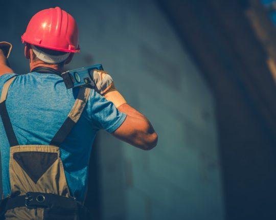 pracownik na budowie z poziomicą